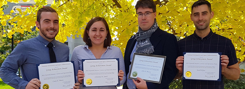 photo of professor and three graduate students all holding certificates from NASA