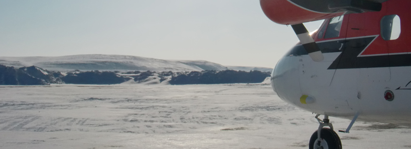 photo of an airplane nose with an Arctic landscape in the background